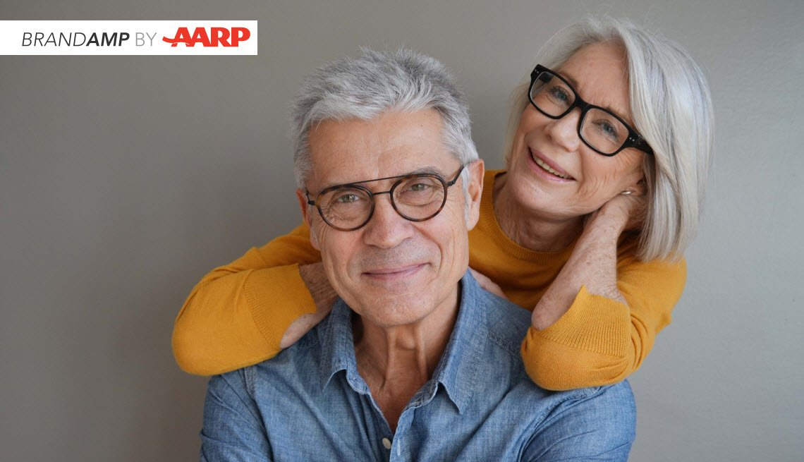 confident and relaxed silver haired woman with glasses leans on her smiling husband ir