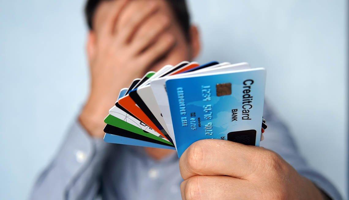 Hombre sostiene tarjetas de crédito en una mano y se cubre el rostro con la otra.