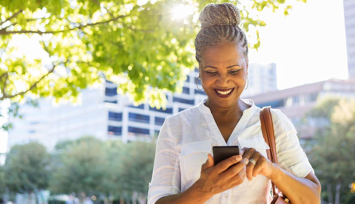 Mujer riendo y mirando a su teléfono móvil.