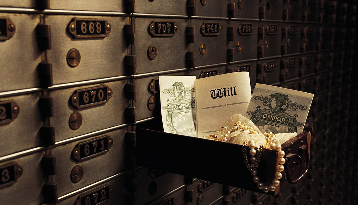 Open safe deposit box in bank vault revealing contents including will, stock certificates and jewelry