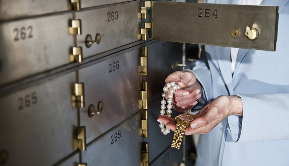 Woman holding necklace and gold watch, standing next to open safety deposit box