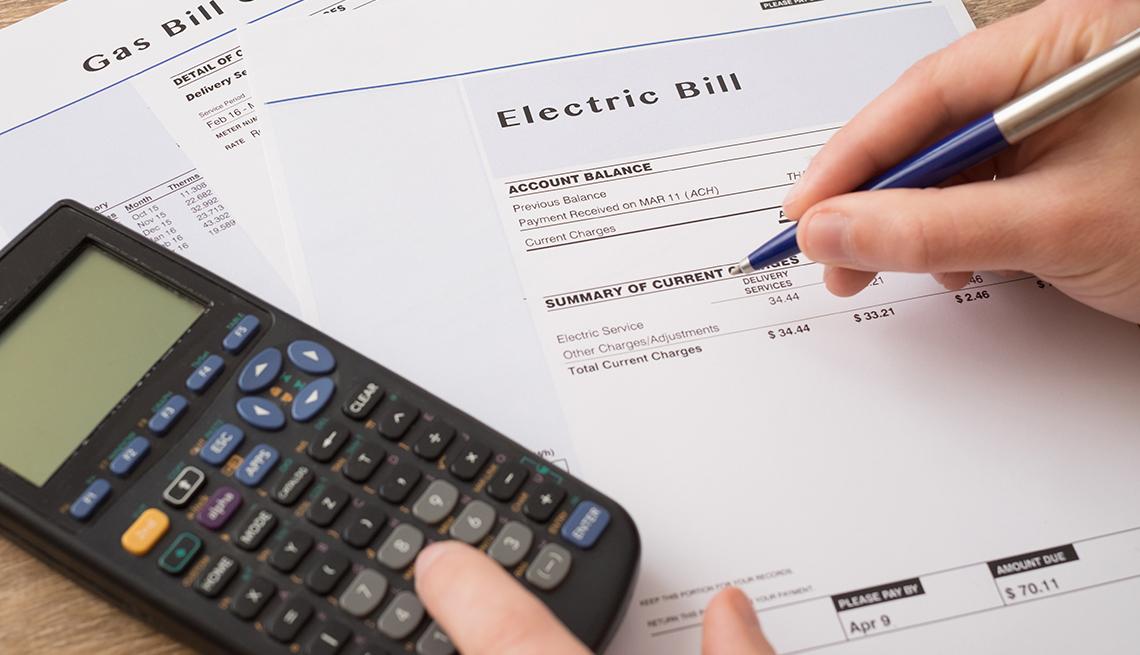 Manos con un lapicero, una calculadora y facturas de la energía.