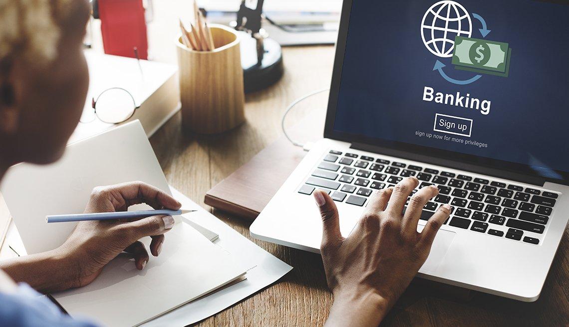 Mujer mirando la pantalla de una computadora con servicios bancarios.