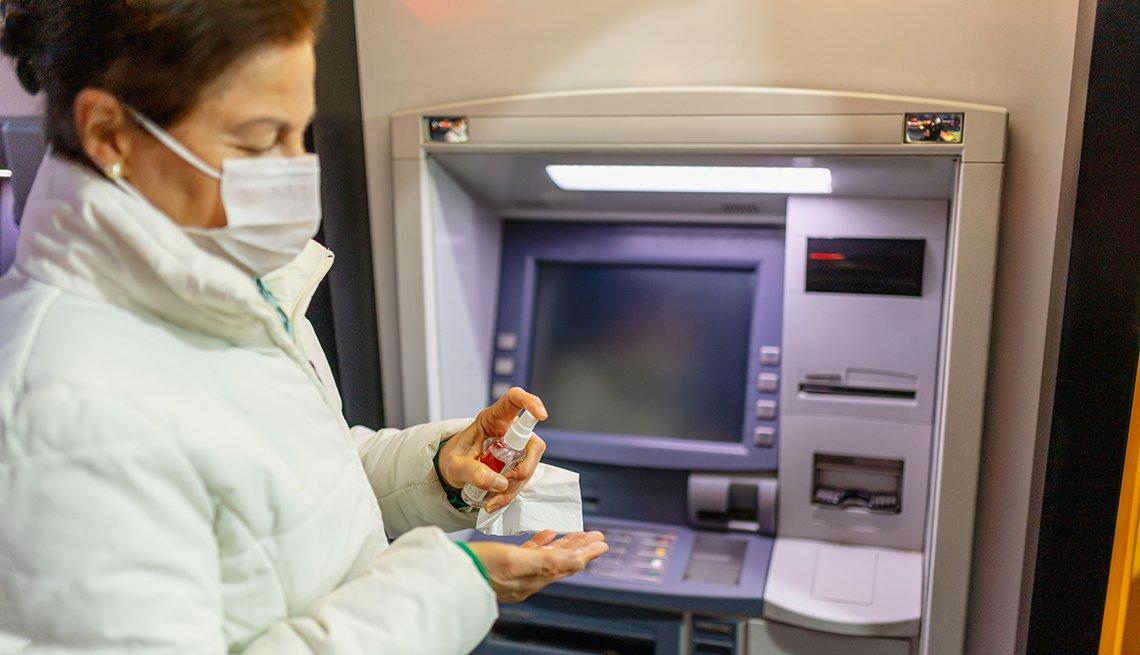 Mujer con una máscara en la boca frente a un cajero automático mientras se pone desinfectante en las manos.