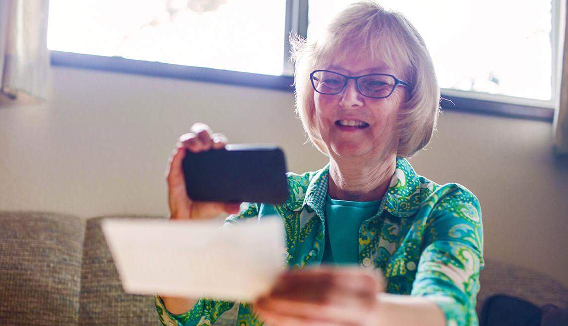 Señora mayor tomando una foto a un cheque para hacer un depósito digital
