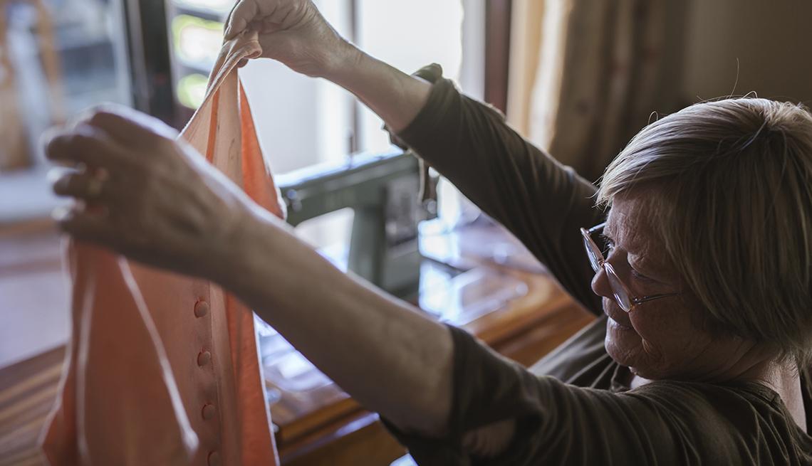 Señora mayor examinando un vestido que sostiene con sus manos estirada hacia arriba.