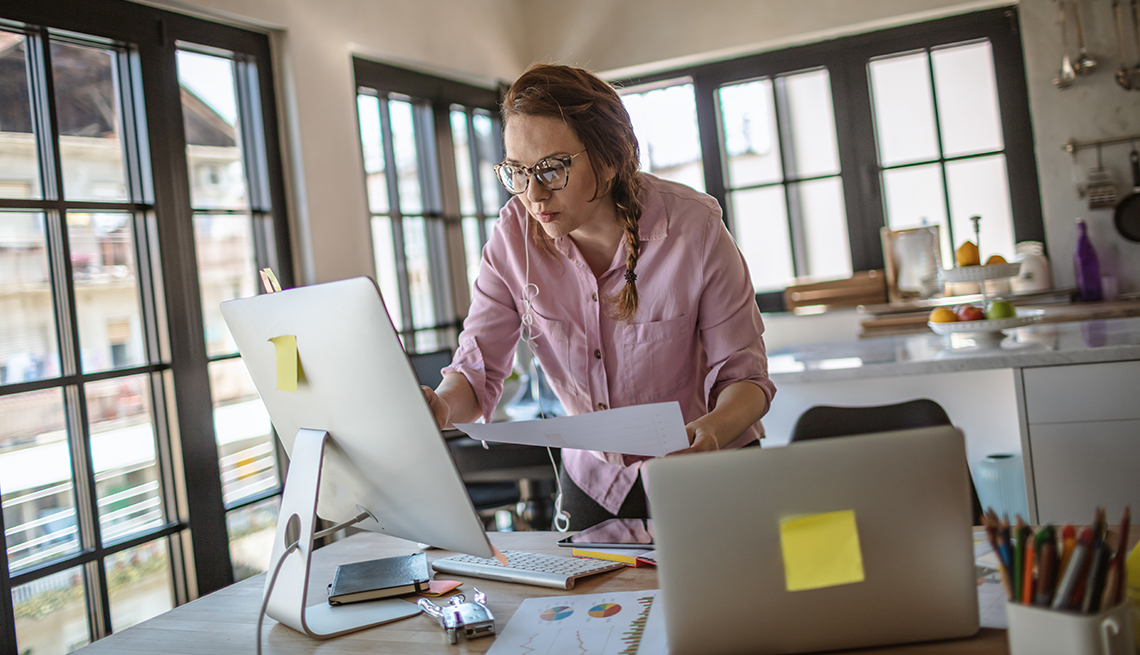 woman working from home stands at dining table looking at computer screen while holding papers