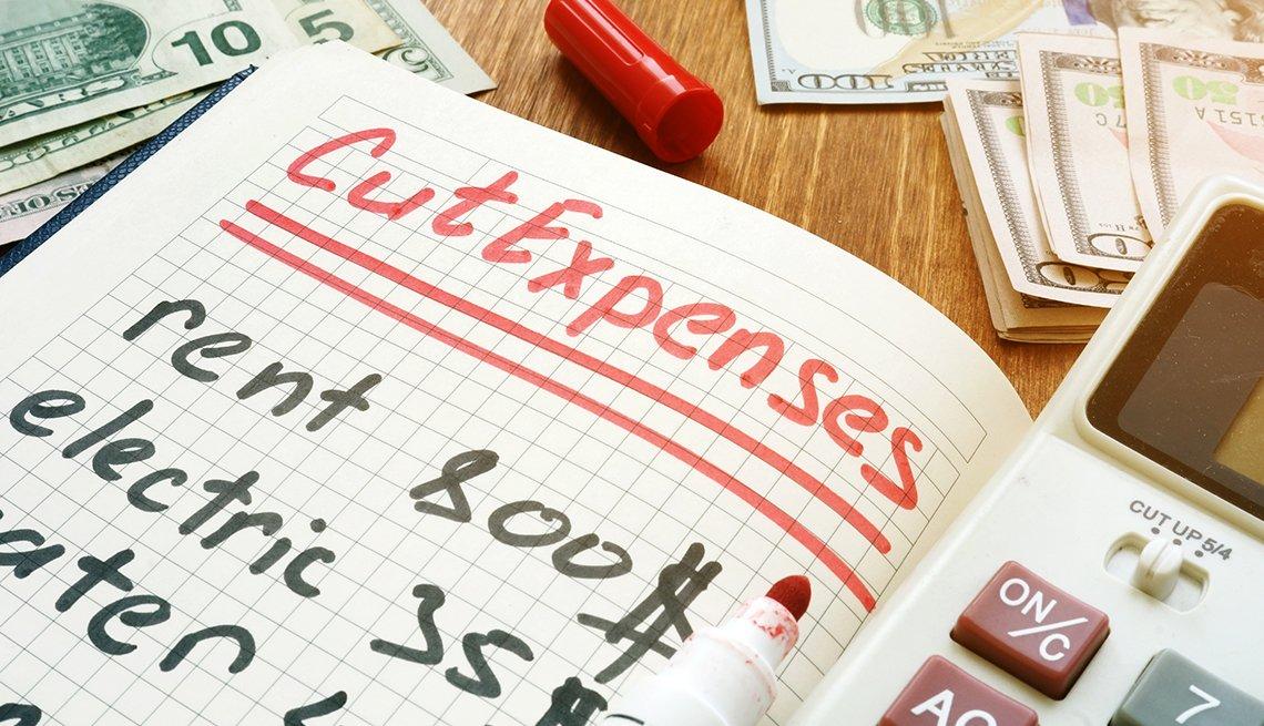 Hoja con una lista en inglés de gastos para cortar, al lado de una calculadora, dinero y un marcador.
