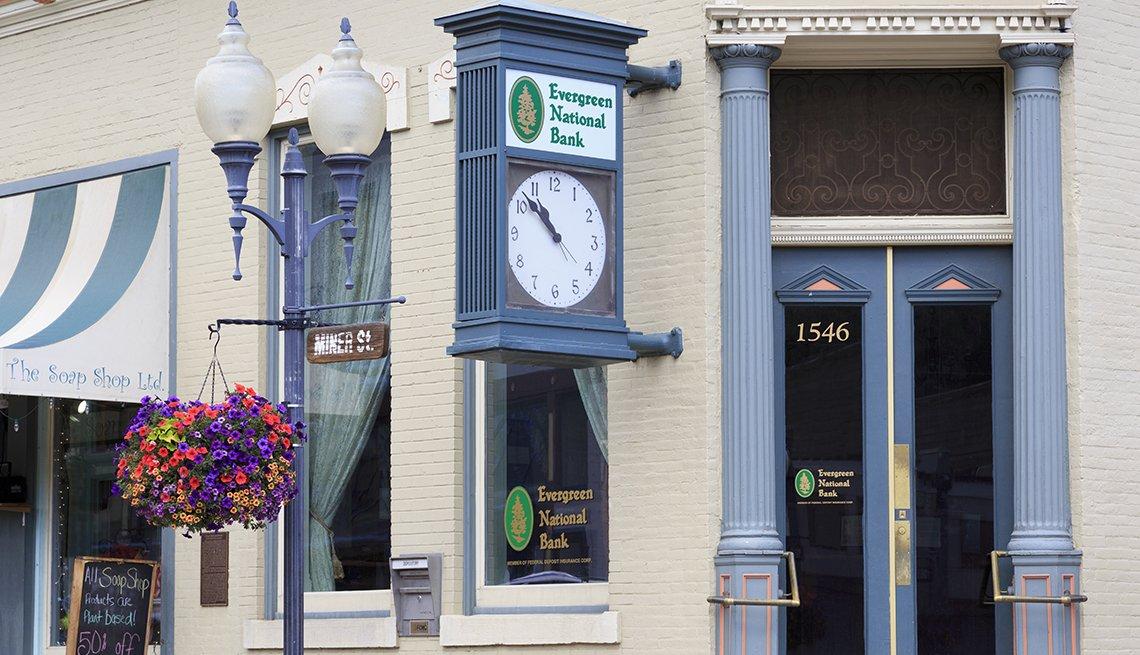 Exterior de la fachada de un banco en una ciudad con un reloj y un letrero que dice Evergreen National Bank.