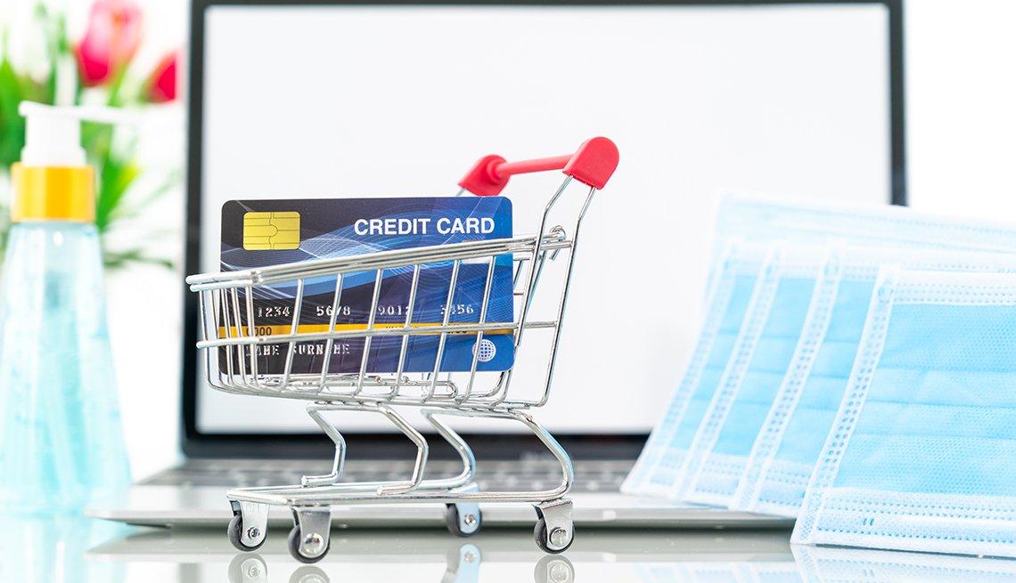 Escritorio con un computador portátil, al lado de máscaras faciales, un desinfectante y un carrito de compras miniatura llevando una tarjeta de crédito.