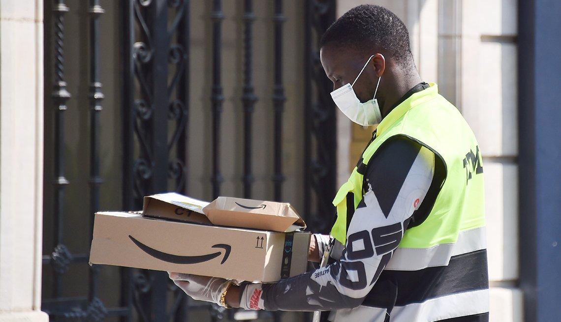 Conductor de Amazon usa mascarilla y guantes mientras entrega unos paquetes