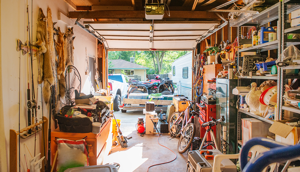 Garaje con estantes llenos con herramientas, elementos de aseo, decoraciones de temporada, juguetes, y equipos para deportes.