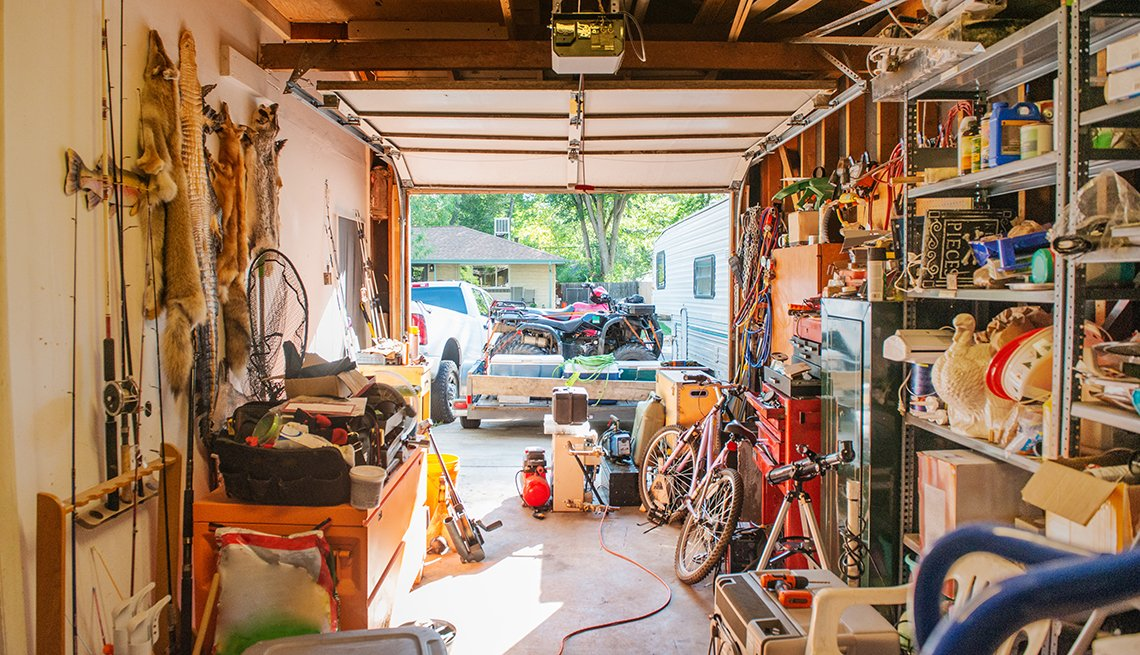 a garage lined with shelves full of things stored at home including tools cleaning supplies holiday decorations and sporting equipment with garage door open