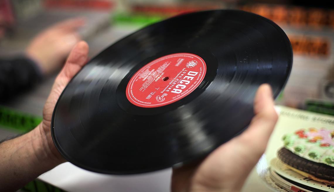 closeup of hands holding a vintage vinyl record album