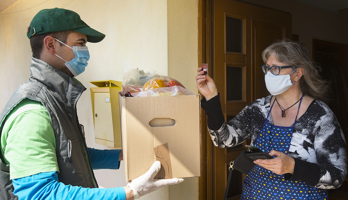 woman wearing surgical mask standing in house door way paying for home delivery of groceries with credit card