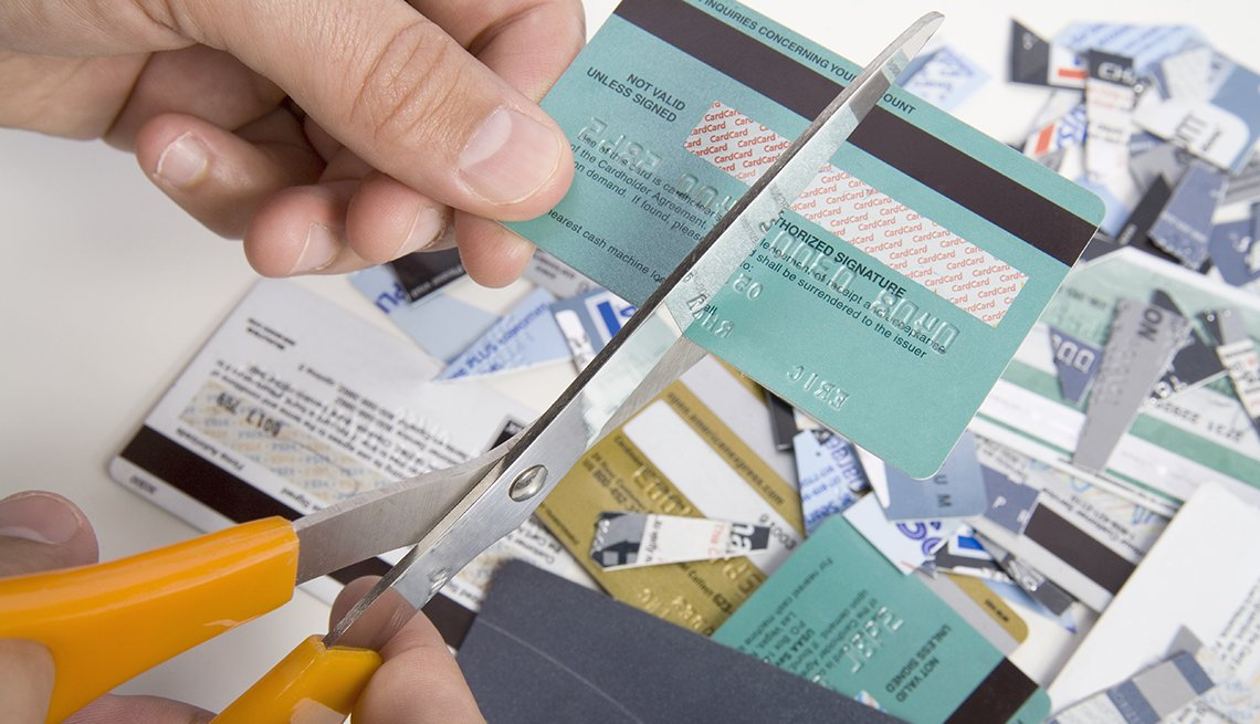 Close up of hands using scissors to cut up a credit card over pile of cut cards