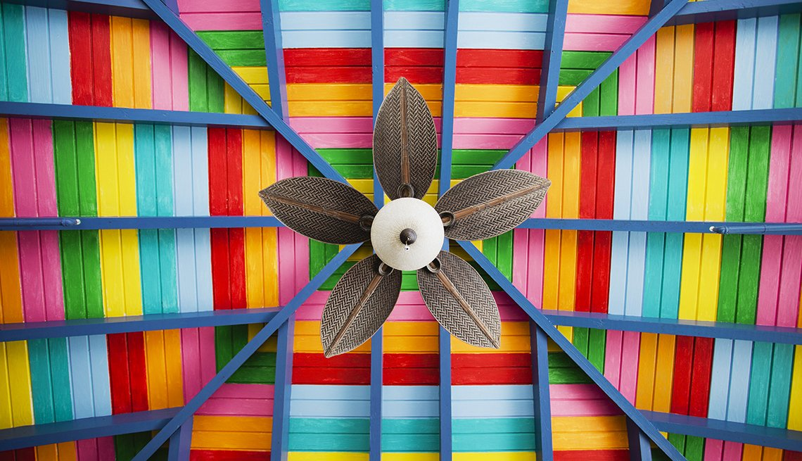 looking up at petal-shaped fan on multi-coloured ceiling