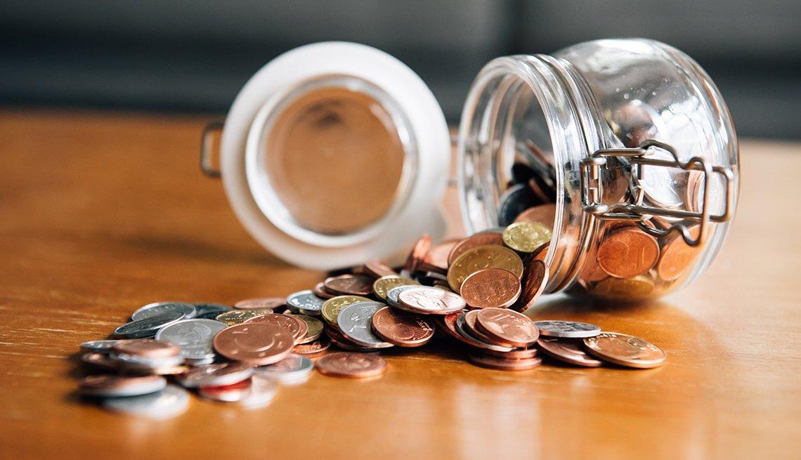 Jarra de lado con la tapa abierta sobre una mesa donde caen las monedas.