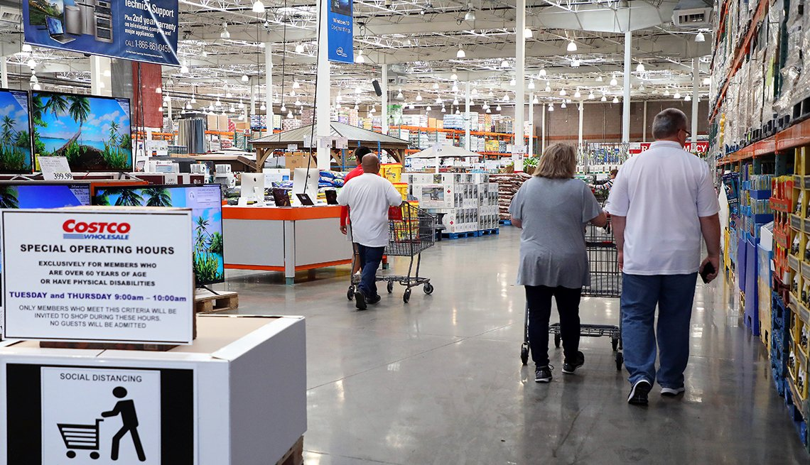 A sign inside Costco greets shoppers during the coronavirus pandemic with a social distancing message about special hours for customers over 60 years old