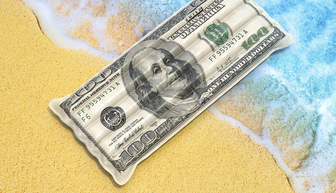 Billete de 100 dólares arrastrado por una ola a la arena.