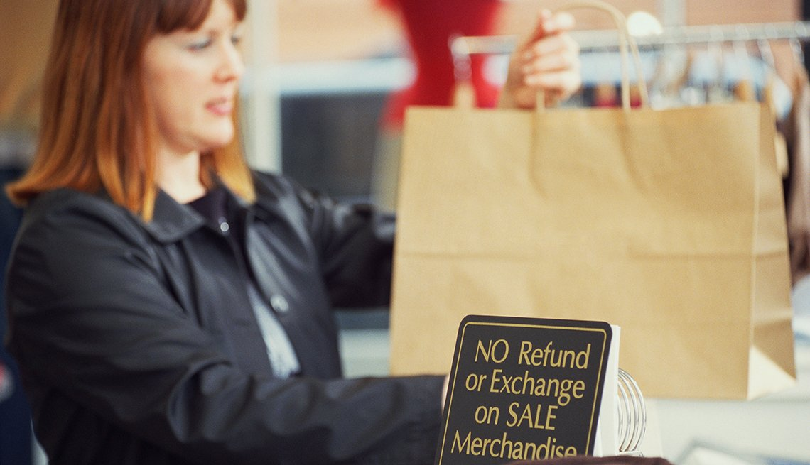 Mujer en la sección de retorno de compras de una tienda donde hay una letrero que anuncia sin reembolsos o intercambio de mercancía