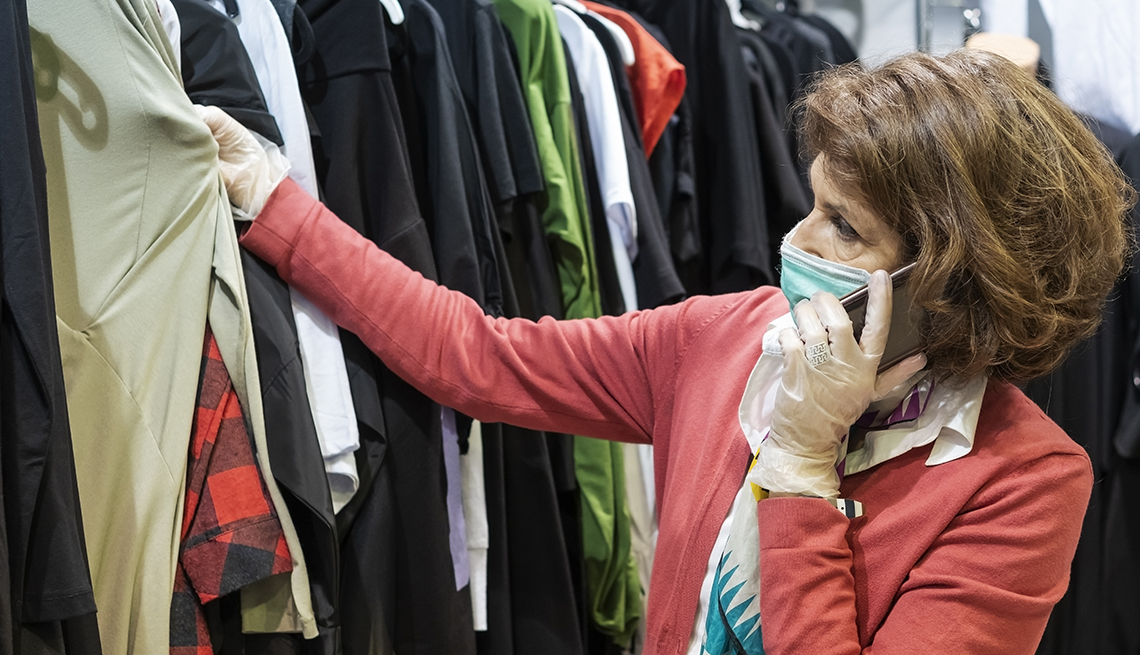 shopper looking at used clothes on a store rack while wearing mask and gloves during the coronavirus pandemic