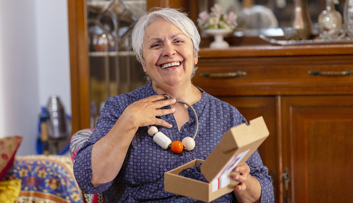 smiling woman holding up a gift necklace that was delivered to her home