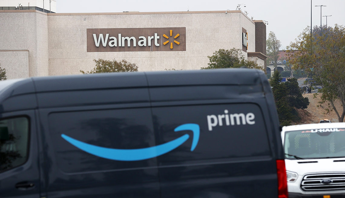 An Amazon Prime delivery van sits parked near a Walmart store.