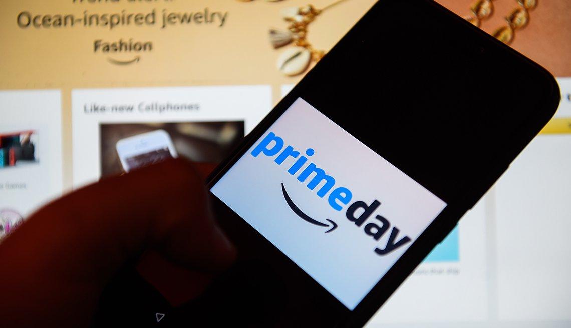 Persona sosteniendo un teléfono móvil y en la pantalla tiene el logo de Prime Day