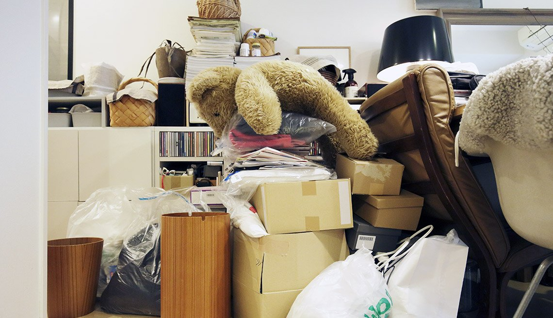 Oso de peluche, computador, cajas, y bolsas amontonadas en un cuarto.