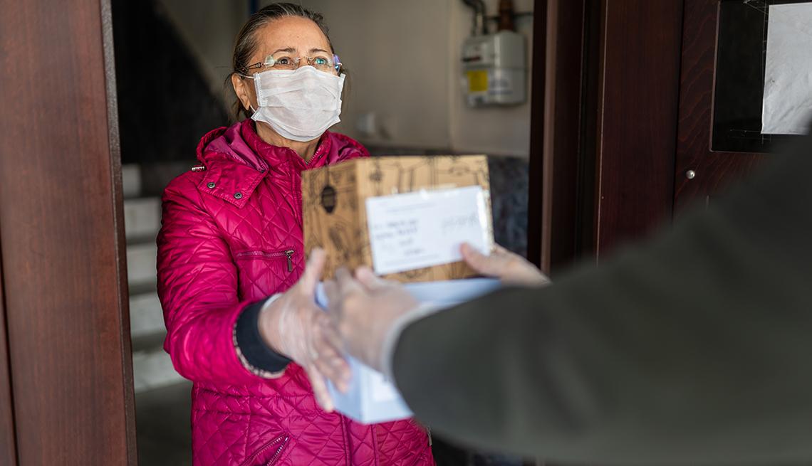 Mujer con guantes y mascarilla devolviendo un paquete a un cartero.