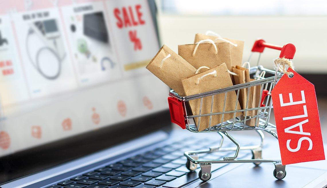 Computador portátil con un carrito de compras miniatura que tiene un letrero que dice oferta.