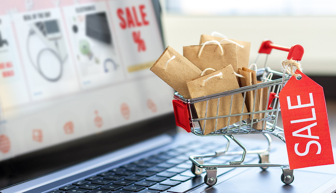 A laptop computer with an online store on screen and a miniature shopping cart full of paper gift bags, representing a cyber-shopper prepared for holiday sales deals
