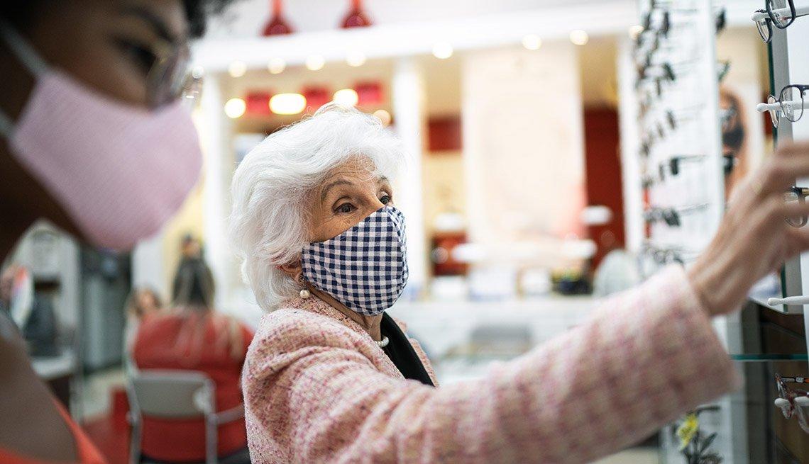 Mujer viendo lentes recetados en una tienda mientras usa la mascarilla.