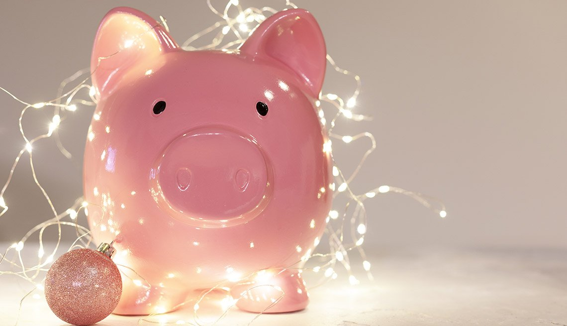 pink piggy bank with pink christmas bauble and christmas lights on white background