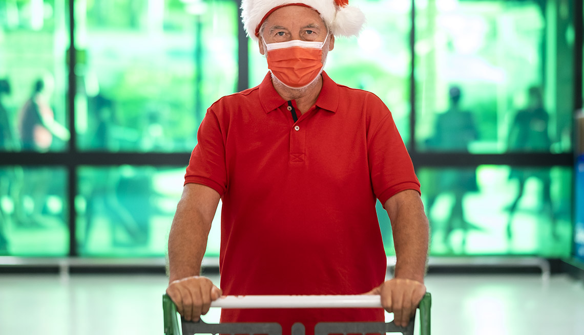 man with santa hat wearing a protective face mask due to covid-19 is pushing a shopping cart