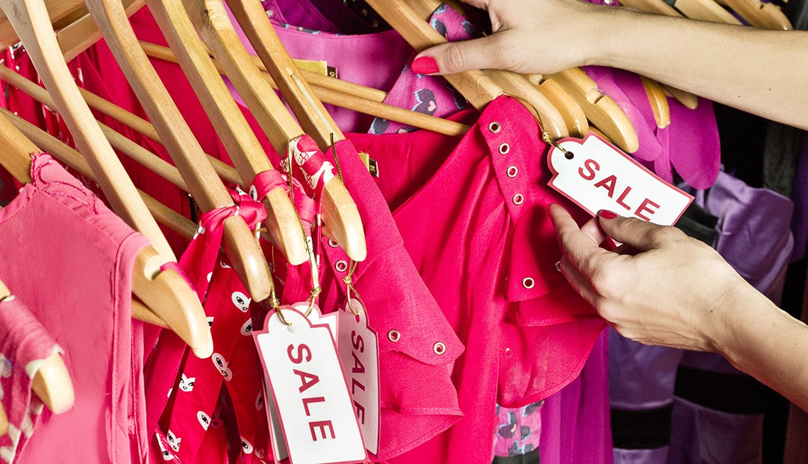close up on the hands of a shopper looking through a store rack of pink clothing marked with sale tags