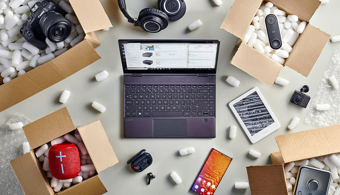 overhead photo of a laptop computer surrounded by online shopping purchases in open delivery boxes filled with packing peanuts