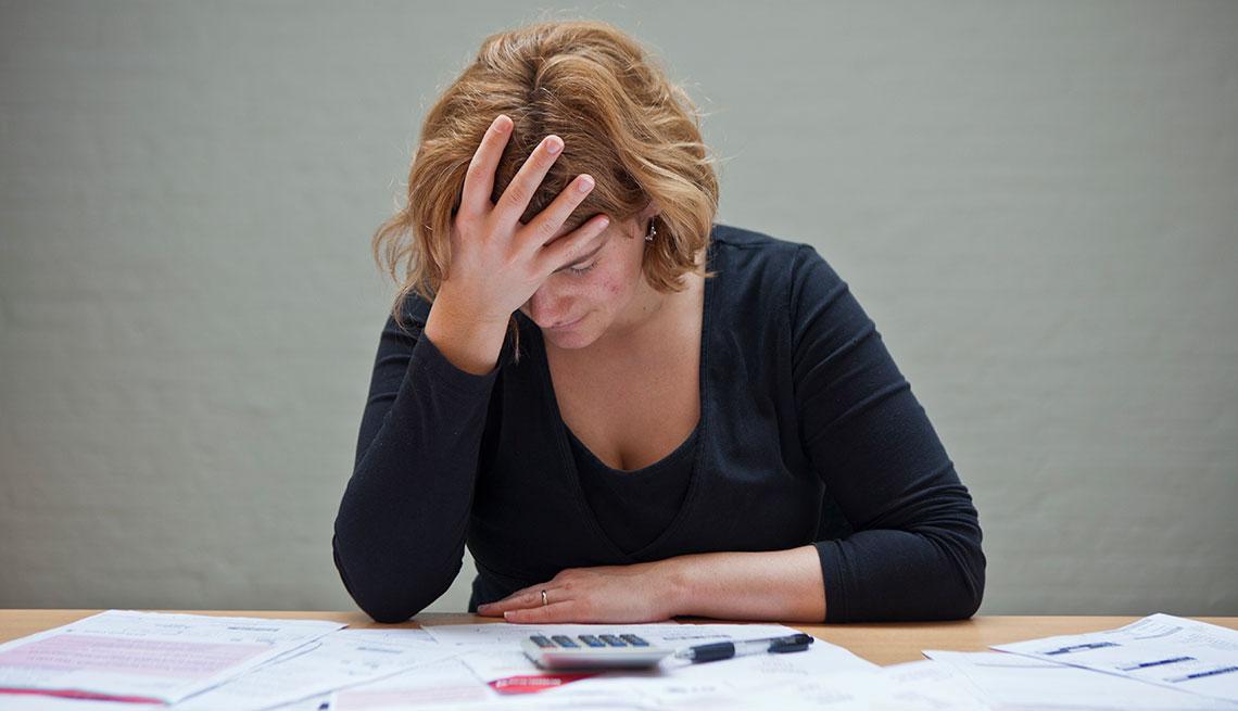Mujer preocupada por las facturas en su escritorio