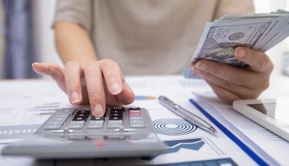 Mujer digitando en una calculadora y sosteniendo un fajo de dólares en la mano.