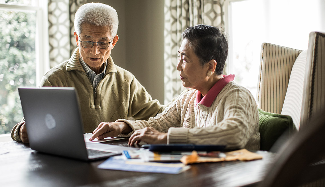 Couple seated at table using laptop to pay bills at home