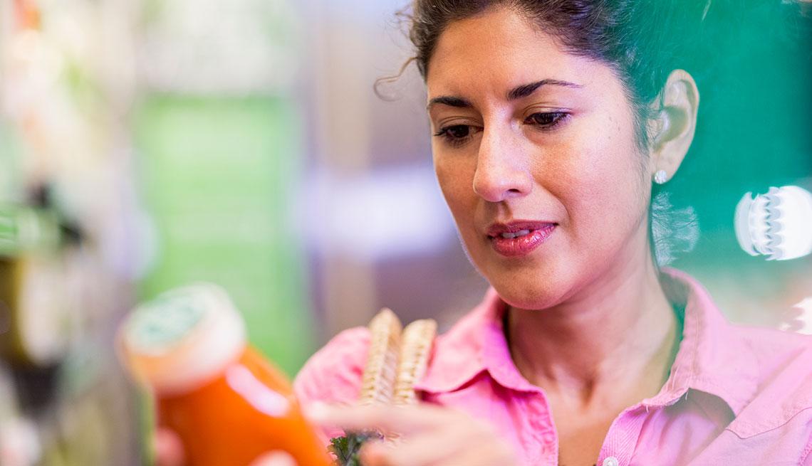 Mujer revisa los ingredientes en la etiqueta de un producto en un supermercado