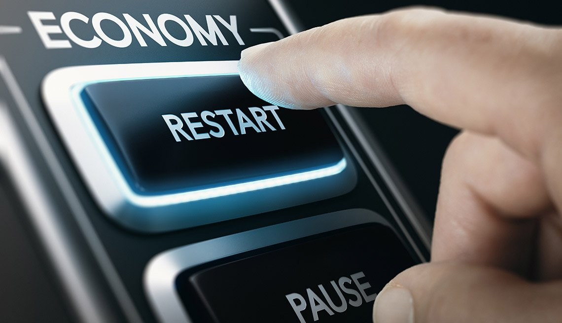 a finger is pressing an economy restart button such as after the global pause caused by the pandemic
