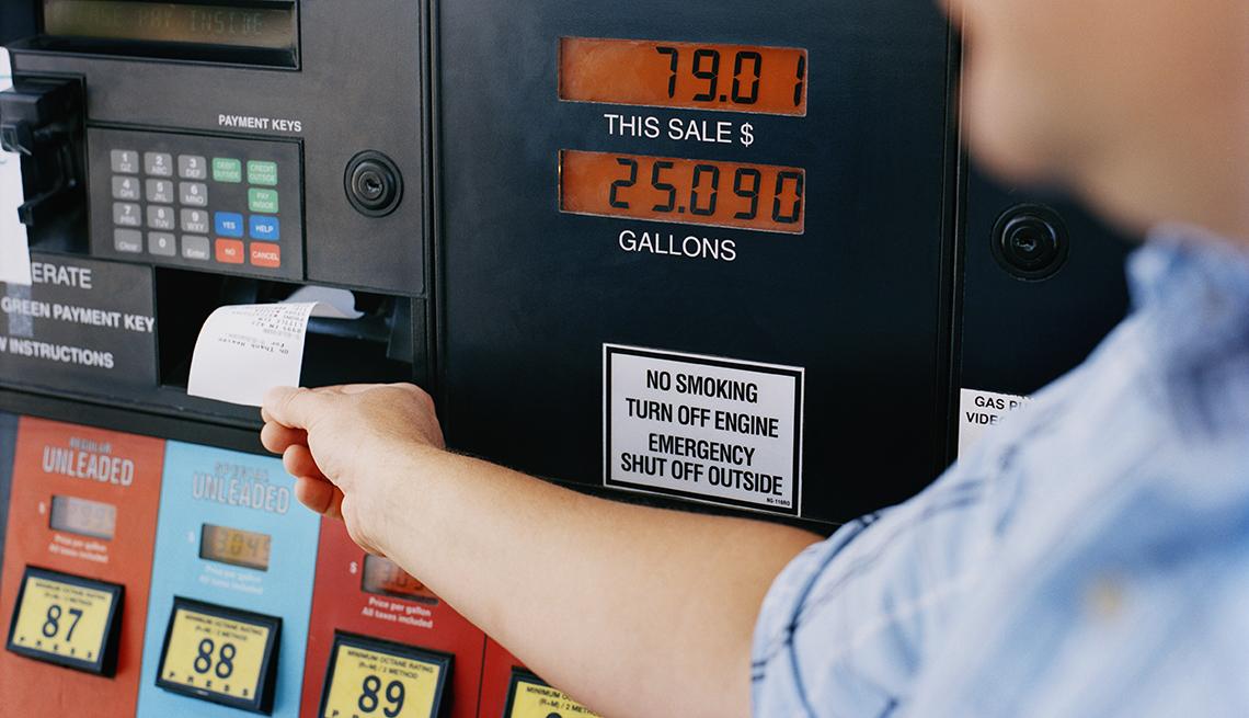 Hombre jalando el recibo de pago de un dispensador de gasolina