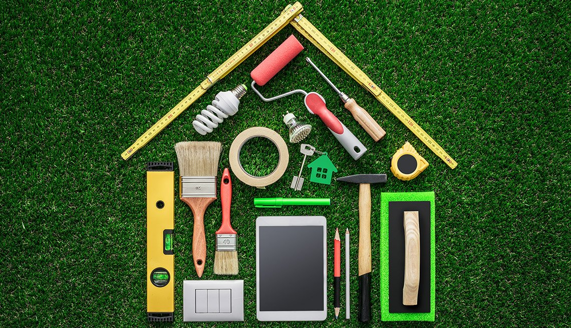 Home remodeling DIY tools spread out on a green grass background in the shape of a house