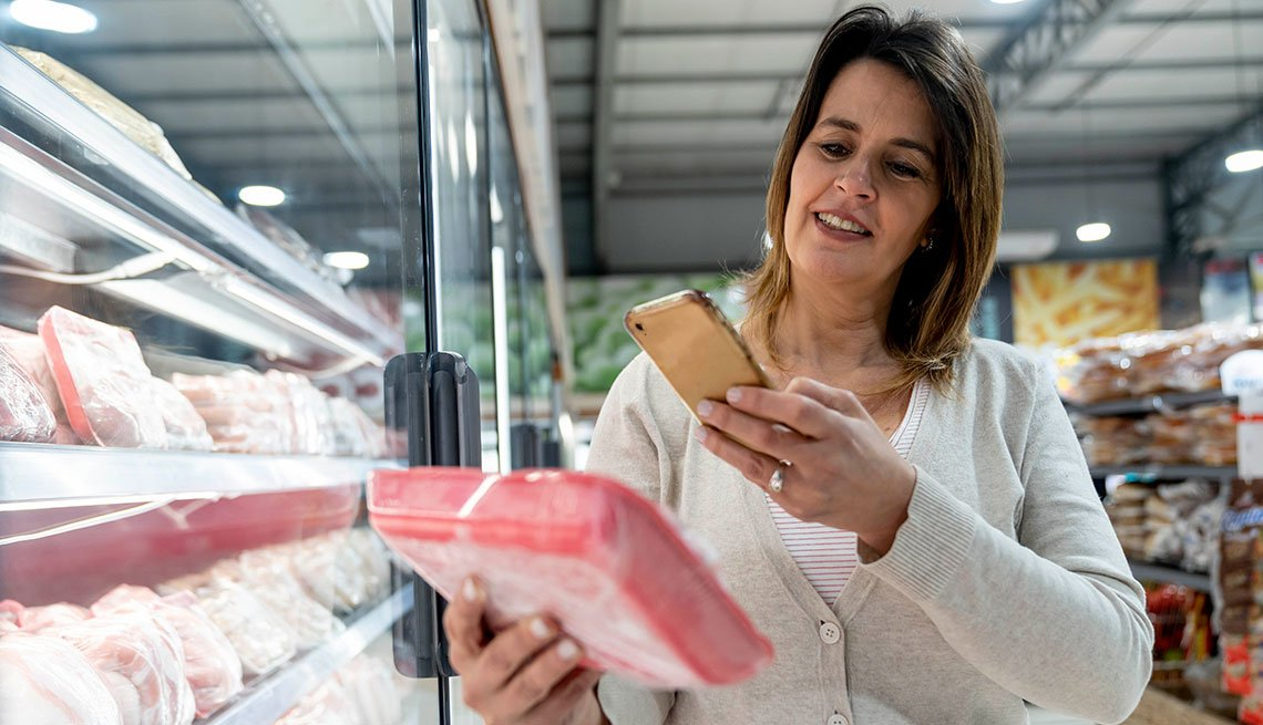 Mujer en un supermercado sostiene un producto y con la otra mano lo escanea con su teléfono.