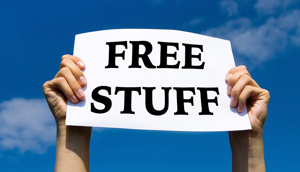 """hands holding up a sign that says """"Free Stuff"""" against a blue sky background"""