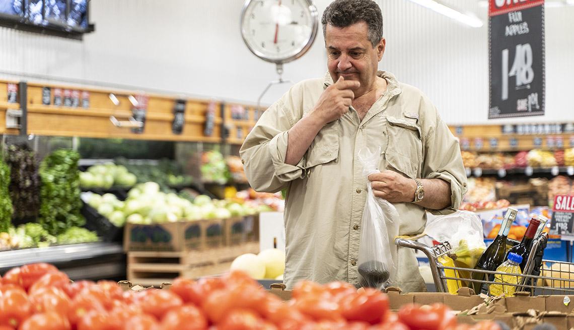 Hombre frente a unos tomates en la sección de vegetales de un supermercado