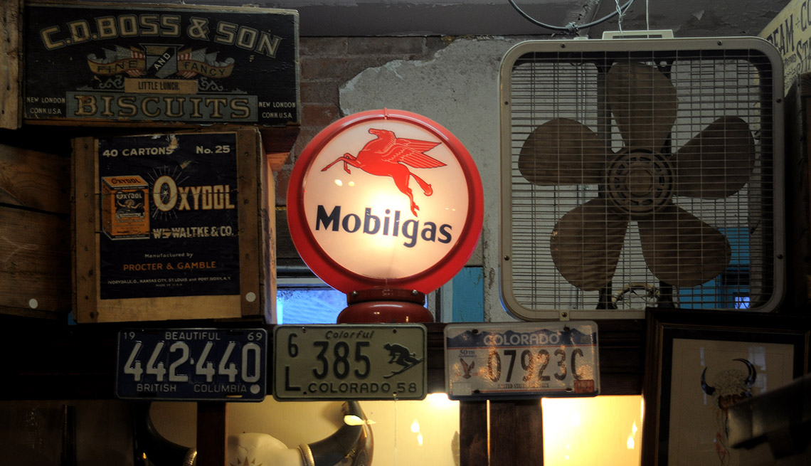 item 4 of Gallery image -  A vintage lit-up Mobilgas gasoline pump dome light is among a display of antiques