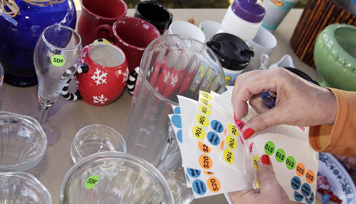 Una mesa de una venta de garaje con vasijas y una mano colocando letreros con precios.